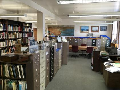 Interior view of a section of the San Pedro Bay Historical Society Archives, showing file cabinets, displayed photos and paintings
